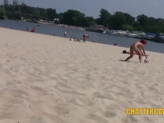 Two nudist girls plays volleyball on a beach full of people with no clothes